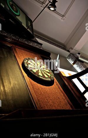 Dartboard im öffentlichen Haus, beleuchtet durch Scheinwerfer an der Decke - Stockfoto