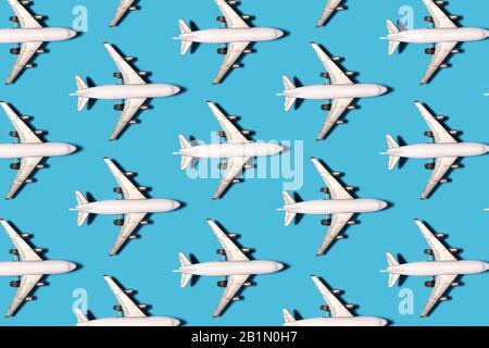 Spielzeugflugzeug mit Schattenmuster auf hellblauem Hintergrund - Stockfoto