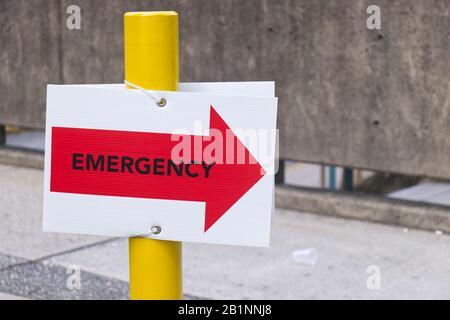 Nahansicht des roten Notsignals mit Richtungspfeil zum Eingang der Notaufnahme - Stockfoto