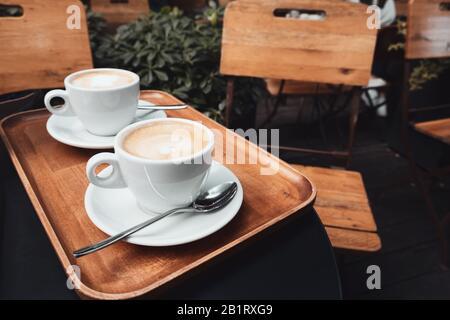 Zwei Tassen Cappuccino mit Latte Art auf Holzhintergrund. Stockfoto