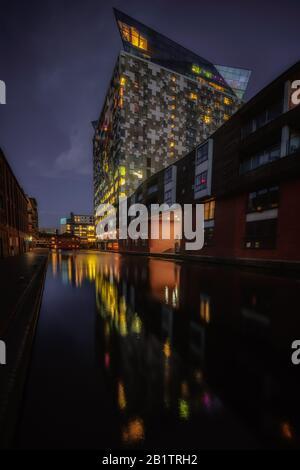 Das Cube Gebäude in Birmingham, das sich nachts in den Kanalwässern widerspiegelt - Stockfoto
