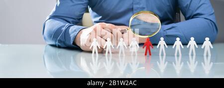 Nahaufnahme DER Handlupe EINES Geschäftsreisenden Über der roten menschlichen Figur Am Schreibtisch - Stockfoto