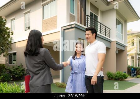 Asian Happy Smile junge Paare geben sich nach Vertragsabschluss mit Immobilienmakler oder Realtor vor ihrem Haus ein, Konzept für Real - Stockfoto