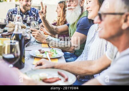 Fröhliche Familie, die beim Barbecue-Dinner im Backyar im Freien Wein isst und trinkt - Reife und junge Leute, die am bbq-sonntagmenü Spaß haben - Essen und Sommer - Stockfoto