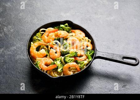 Nahaufnahme von Garnelen und Brokkoli Pasta in Gusseisenpfanne über dunklem Steingrund. Leckeres, gesundes Gericht zum Abendessen. - Stockfoto