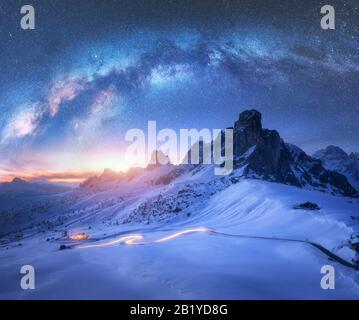 Milchstraße über verschneite Berge und Autoscheinwerfer auf der Straße - Stockfoto