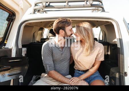 Bild eines positiven fröhlichen jungen, wundervollen Liebespaares im Freien, das sich am Strand im Auto umarmt.