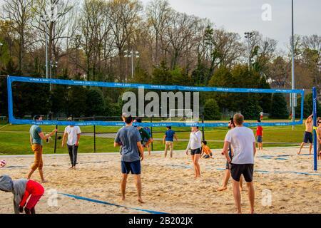 Charlotte, NC/USA - 24. März 2019: Mittelgroßer Schuss Aufhol-Volleyball-Spiel auf einem Sandplatz an einem sonnigen, warmen Vorfrühling im Freedom Park. - Stockfoto