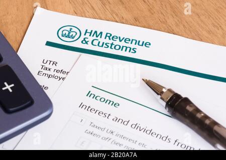 London, Großbritannien - 25. März 2012. Abschluss der Steuererklärung in Großbritannien mit Taschenrechner und Stift - Stockfoto