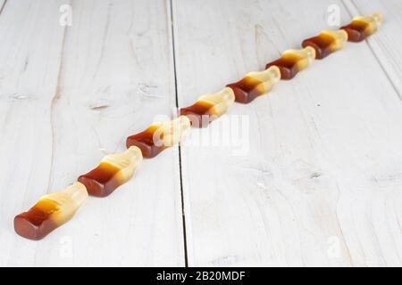 Gruppe von acht ganzen süßen Gelee Cola auf weißem Holz - Stockfoto