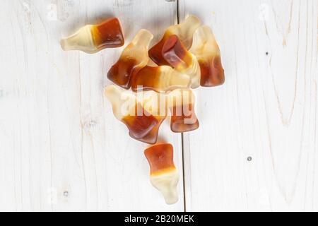 Viele ganze süße Gelee Cola schmeicheln auf weißem Holz - Stockfoto
