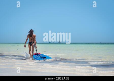 Schöne Frau mit einem Surfbrett, das ins Wassermeer eindringt, um sich beim Wassersport aufzuhalten. Kristallklares türkisfarbenes Wasser und weißer Strand l - Stockfoto