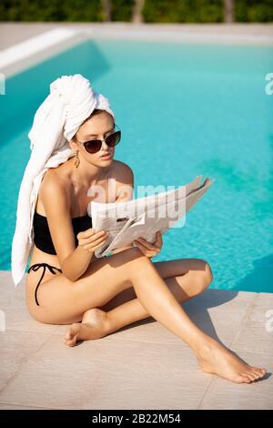 """Schöne junge Frau mit Handtuch auf der Zeitung """"Hair Reading"""" in der Nähe des Hotelpools - Stockfoto"""