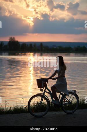 Silhouette eines hübschen Mädchens, das mit einem Fahrrad am See entlang bei schönem Sonnenuntergang, lilafarbenem Horizont und Sonnenweg auf dem Wasser reitet, ruhige Momente, Kopieraum