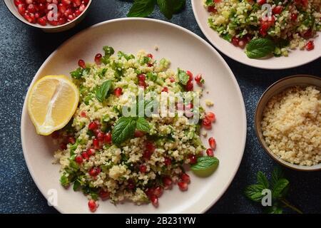 Gesunder Salat mit Couscous, frischer Minze, Gurke, Granatapfel, Zitrone und Olivenöl. Östliche Küche. Veganes Lebensmittelkonzept. Traditionelle israelische Küche - Stockfoto