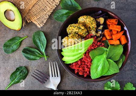 Gesunde vegane buddha-schüssel mit Falafeln, Rübenquinoa, Avocado und Gemüse auf dunklem Steingrund. Gesundes Esskonzept. Overhead-Szene. - Stockfoto