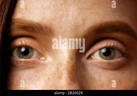 Schöne weibliche Augen. Nahaufnahme eines gerippten Schusses einer jungen kaukasischen Frau mit Freckeln, ohne Makeup. Augenheilkunde, Sehkonzept.