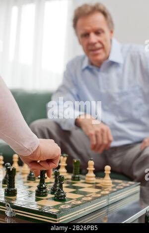 Reifer Mann, der in einem hellen Wohnzimmer Schach spielt - im Vordergrund die Hand der Frau - Stockfoto