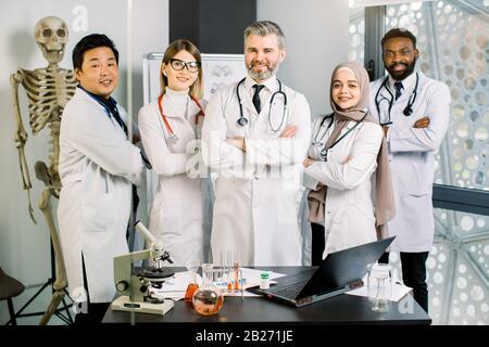 Lächelnde multiethnische Gruppe von Ärzten, Wissenschaftler im modernen Labor mit leitender männlicher Führungskraft. Team von jungen Ärzten mit reifen Einwohnern oder Studenten - Stockfoto