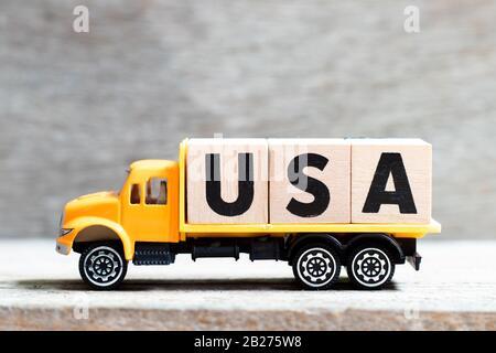LKW hält Buchstabenblock im Wort USA (Abkürzung der Vereinigten Staaten von Amerika) auf Holzhintergrund - Stockfoto