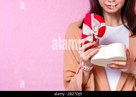 Geschenkschachtel in Form eines Herzens in den Händen eines jungen asiatischen Mädchens. Auf einem rosa isolierten Hintergrund. Konzentrieren Sie sich auf die Schachtel - Stockfoto