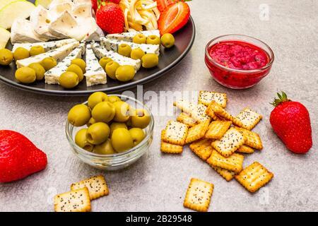 Köstlicher Snack mit verschiedenen Käsesorten. Bayerischer Käse mit Jalapeno-Paprika, Blauschimmelkäse und geräuchertem Schweinekäse, Obst und Oliven, Marmelade, cra - Stockfoto