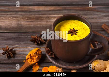 Goldene Milch oder turmartige Latte aus Curcuma, Sternanis, Ingwer und Zimt auf rustikalem Holztisch. Gesundes Getränk. Nahaufnahme - Stockfoto