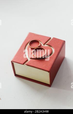 Zwei Ringe für die emotionale Bindung auf dem roten Herzgeschenkkasten - Stockfoto