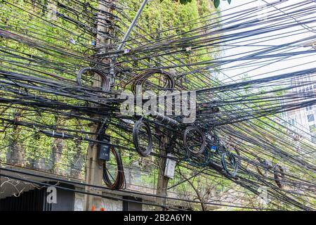 Unordentliche und unsaubere elektrische Kabel, die an einem Strompfosten in Thailand hängen - Stockfoto
