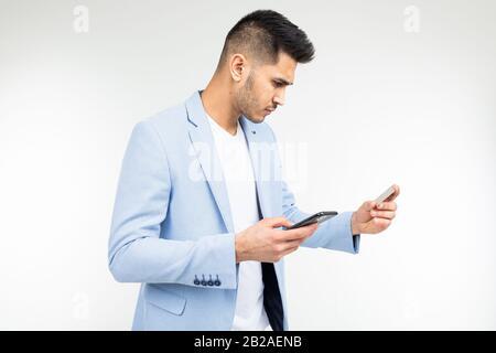 Gutaussehender Mann bestellt Online-Einkäufe über ein Smartphone, das eine Kreditkarte in seinen Händen hält - Stockfoto