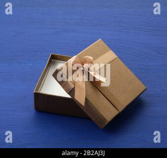 Offener brauner, quadratischer Karton, leerer Karton, Artikel liegt auf blauem Holzhintergrund, nah oben.