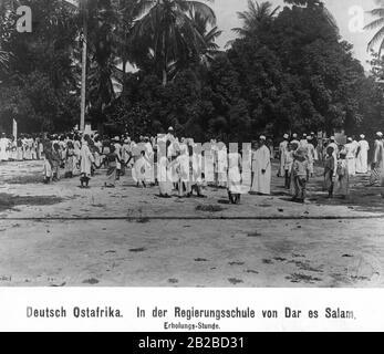 Entspannungsklasse in der Regierungsschule Daressalam in Deutsch Ostafrika. Kinder sind auf dem Spielplatz in typisch schwarzafrikanischer, arabischer und europäischer Kleidung zu sehen. - Stockfoto