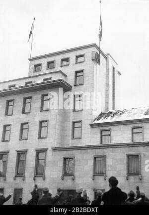 Siegesfahnen werden auf dem Dach der neuen Staatskanzlei als Zeichen für den Sieg im Saarland gehisst. Rechts befindet sich die Hakenkreuzfahne, links die Reichdienstflaggen des Deutschen Reiches. Anhänger machen den Nazi-Salut beim Zuhören. - Stockfoto