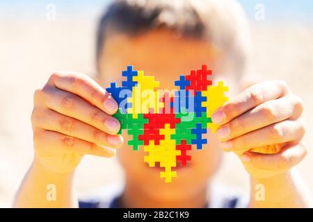 Weltautismus Bewusstsein Tag Konzept. Junge, der buntes Puzzleherz vor seinem Gesicht hält - Stockfoto