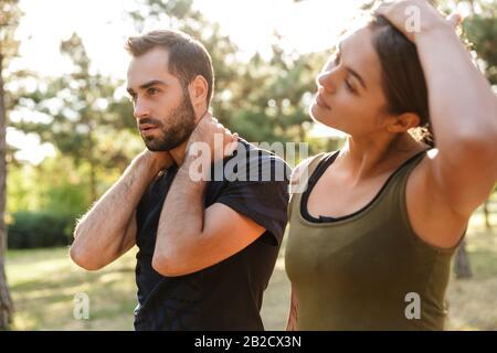 Bild einer jungen, stark konzentrierten Sportfrau und eines Mannes machen Dehnübungen im Freien im grünen Park. - Stockfoto