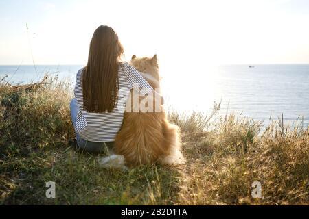 Junge schöne Frau mit langen Haaren, die mit Collie Hund spazieren geht. Draußen im Park, in der Nähe des Meeres, Sommerbeatch - Stockfoto
