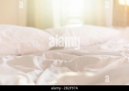 Schließen Sie morgens weiße Bettlaken und Kissen im Hotelzimmer mit Sonnenlicht von Fenstern - Stockfoto