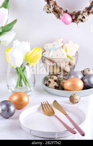 Ostertischeinstellung mit Tulpen, ostereiern, Plätzchen und Teller mit Besteck auf weißem Tisch - Stockfoto