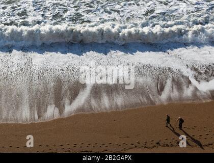 Altes Paar, das am Sandstrand spazieren geht, mit weißer Brandung von brechenden Wellen, Luftbild, Dorset, England, Großbritannien