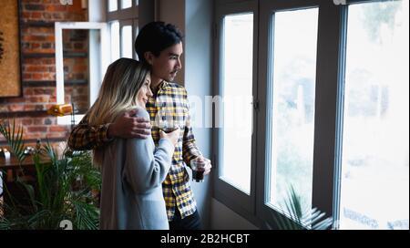 Junges Paar, das durch das Fenster blickt Stockfoto