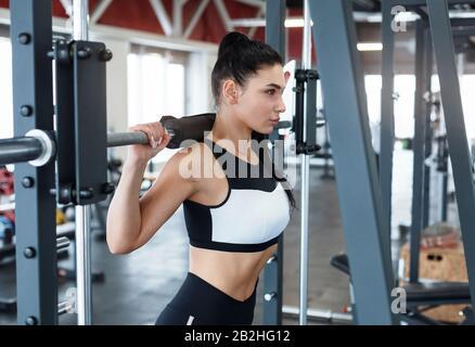 Bodybuilding-Workout. Junge Frau mit Trainingsgerät im Fitnessstudio - Stockfoto