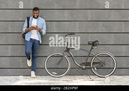 Junger Schwarzer Mann Mit Smartphone, Neben Seinem Fahrrad Im Freien Stehend Stockfoto