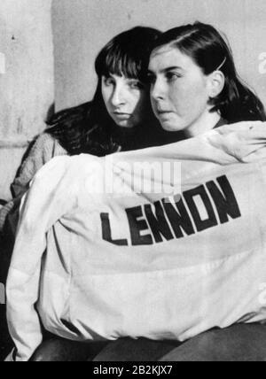 Zwei John Lennon-Fans halten sich in Liverpool während einer Hommage an die ehemalige Beatle warm, die vor einem Jahr in New York ermordet wurde. - Stockfoto