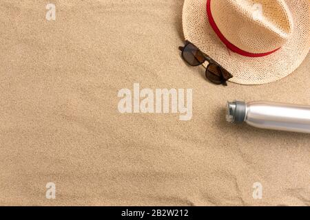 Strohhut und Flasche Wasser auf Sandgrund. Strandurlaubskonzept .Top View mit Copy-Platz. - Stockfoto