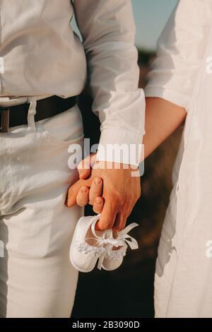 Frisch verkleidetes Paar, das in weißer Kleidung gekleidet ist, geht Hand in Hand und hält dabei ein Paar Babyschuhe - Stockfoto
