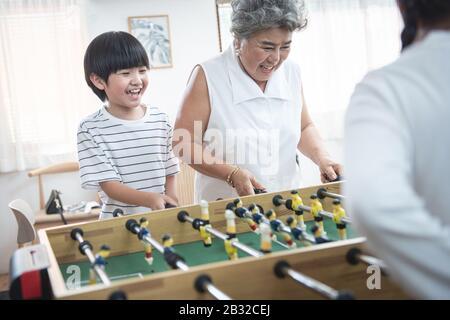Gruppe der Vielfalt altert Familie, die glücklich zusammen Fußball-Tischspiel spielt. Großmutter spielt zusammen mit ihren Kindern zu Hause