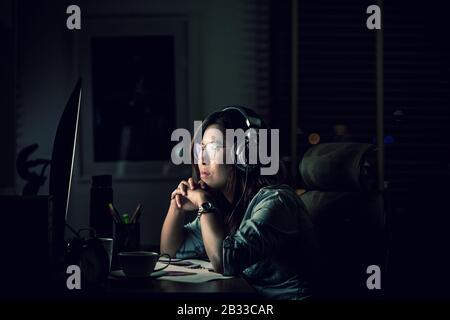 Portrait der asiatischen Geschäftsfrau, die spät am Tisch sitzt und hart arbeitet, mit der Vorderseite des Computerdesktops am Arbeitsplatz, mit ernsthaften Aktionen, Arbeit ha - Stockfoto
