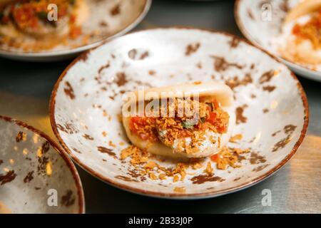 Gedämpftes Kebab mit Rotan in einem Bun. Das Gericht liegt in einer runden Platte. Bereit zum servieren. - Stockfoto