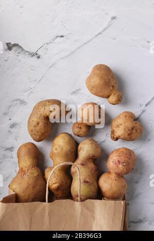 Hässliche Kartoffeln aus biologischem Anbau in einer Papiertüte auf Marmorgrund, Konzept für organisches Gemüse, Konzept für Nullabfälle - Stockfoto