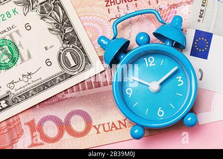 Der Wecker liegt auf verschiedenen Geldmitteln, ein Blick von oben. Konzeptzeit - Geld